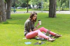Καφές κατανάλωσης γυναικών σε ένα πάρκο Στοκ φωτογραφίες με δικαίωμα ελεύθερης χρήσης