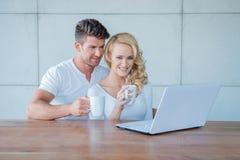 Καφές κατανάλωσης ζεύγους και ανάγνωση σε ένα lap-top Στοκ Εικόνα