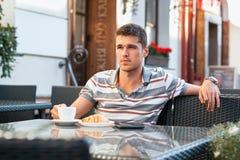 Καφές κατανάλωσης νεαρών άνδρων με croissant Στοκ Εικόνα