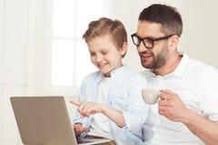 Καφές κατανάλωσης πατέρων και χρησιμοποίηση του lap-top ενώ με λίγο γιο στο σπίτι Στοκ εικόνα με δικαίωμα ελεύθερης χρήσης
