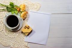 Καφές με τα τριαντάφυλλα και δώρο στον αγροτικό πίνακα στοκ εικόνες