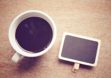 Καφές με τον πίνακα στον πίνακα με το αναδρομικό φίλτρο στοκ φωτογραφίες