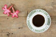 Καφές με το λουλούδι plumeria στο ξύλινο υπόβαθρο σανίδων Στοκ Φωτογραφία