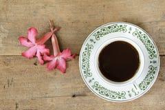 Καφές με το λουλούδι plumeria στο ξύλινο υπόβαθρο σανίδων Στοκ Εικόνες