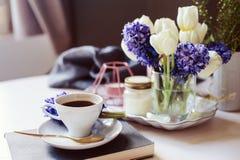 Καφές πρωινού, διακοσμήσεις άνοιξη στο σπίτι στον πίνακα στο σύγχρονο Σκανδιναβικό ύφος με τα λουλούδια και αρωματικά κεριά Στοκ Εικόνα