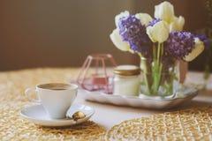 Καφές πρωινού, διακοσμήσεις άνοιξη στο σπίτι στον πίνακα στο σύγχρονο Σκανδιναβικό ύφος με τα λουλούδια και αρωματικά κεριά Στοκ Φωτογραφία