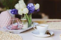 Καφές πρωινού, διακοσμήσεις άνοιξη στο σπίτι στον πίνακα στο σύγχρονο Σκανδιναβικό ύφος με τα λουλούδια και αρωματικά κεριά Στοκ Εικόνες