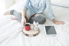 Καφές πρωινού κατανάλωσης κοριτσιών σε μια άσπρη ταμπλέτα ανάγνωσης κρεβατιών στις υψηλές γυναικείες κάλτσες Στοκ φωτογραφία με δικαίωμα ελεύθερης χρήσης