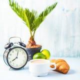 Καφές πρωινού σε ένα άσπρο φλυτζάνι Croissant σε ένα ελαφρύ υπόβαθρο ξυπνήστε με ένα cheerfulness προγευμάτων ξυπνητηριών, ένα υγ στοκ φωτογραφίες