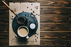 Καφές σε έναν ξύστη με ένα φλυτζάνι σε ένα σκοτεινό υπόβαθρο με την κρέμα στοκ φωτογραφία με δικαίωμα ελεύθερης χρήσης