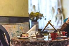 Καφές σε έναν Τούρκο σε έναν πίνακα με ένα κομμάτι cheesecake Στοκ Εικόνες