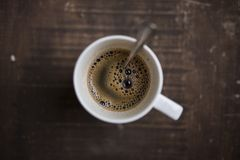 Καφές σε ένα άσπρο φλυτζάνι σε ένα ξύλινο υπόβαθρο πυροβοληθε'ν άνωθεν στοκ εικόνα