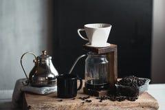 Καφές σε ένα μπουκάλι γυαλιού, σταλαγματιά καφέ, χέρι που κρατά έναν καφέ σταλαγματιάς κατσαρολών στο δωμάτιο στοκ εικόνα