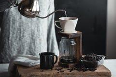 Καφές σε ένα μπουκάλι γυαλιού, σταλαγματιά καφέ, χέρι που κρατά έναν καφέ σταλαγματιάς κατσαρολών στο δωμάτιο στοκ εικόνες με δικαίωμα ελεύθερης χρήσης