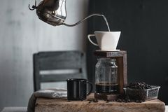 Καφές σε ένα μπουκάλι γυαλιού, σταλαγματιά καφέ, χέρι που κρατά έναν καφέ σταλαγματιάς κατσαρολών στο δωμάτιο στοκ εικόνα με δικαίωμα ελεύθερης χρήσης