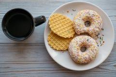Καφές σε μια μαύρη κούπα και donuts με τις γκοφρέτες σε ένα πιάτο Στοκ εικόνα με δικαίωμα ελεύθερης χρήσης