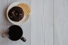 Καφές σε μια μαύρη κούπα και doughnut με την γκοφρέτα σε ένα πιάτο Στοκ Εικόνες