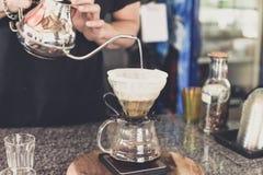 Καφές σταλαγματιάς, χύνοντας νερό barista στο έδαφος καφέ με το φίλτρο στοκ φωτογραφία με δικαίωμα ελεύθερης χρήσης