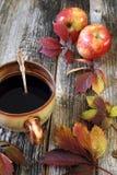 Καφές στη μεγάλη κούπα, τα ζωηρόχρωμα φύλλα και τα κόκκινα μήλα Στοκ εικόνα με δικαίωμα ελεύθερης χρήσης