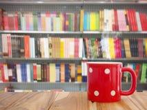 Καφές στον ξύλινο πίνακα πέρα από τα βιβλία στο υπόβαθρο θαμπάδων ραφιών Στοκ φωτογραφία με δικαίωμα ελεύθερης χρήσης