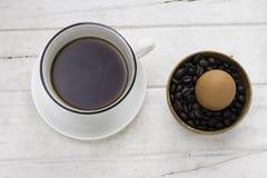 καφές στο άσπρο φλυτζάνι με ένα αυγό και τα φασόλια καφέ στοκ εικόνα με δικαίωμα ελεύθερης χρήσης