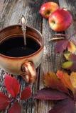 Καφές στο μεγάλο φλυτζάνι, τα ζωηρόχρωμα φύλλα και τα κόκκινα μήλα Στοκ Φωτογραφίες
