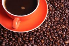 Καφές στο πορτοκαλί φλυτζάνι που περιβάλλεται με τα φασόλια καφέ Στοκ εικόνες με δικαίωμα ελεύθερης χρήσης