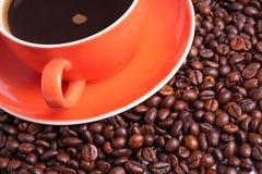 Καφές στο πορτοκαλί φλυτζάνι που περιβάλλεται με τα φασόλια καφέ Στοκ εικόνα με δικαίωμα ελεύθερης χρήσης