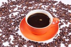 Καφές στο πορτοκαλί φλυτζάνι που περιβάλλεται με τα φασόλια καφέ Στοκ Εικόνα