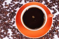 Καφές στο πορτοκαλί φλυτζάνι που περιβάλλεται με τα φασόλια καφέ Στοκ φωτογραφία με δικαίωμα ελεύθερης χρήσης