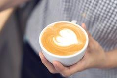 Καφές τέχνης εκμετάλλευσης barista γυναικών latte με τη μορφή καρδιών στο λευκό στοκ εικόνες
