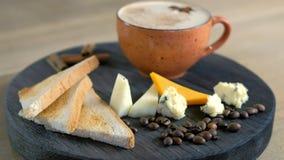 Καφές τυριών με το λειωμένο τυρί, τα κομμάτια του τυριού και τις φρυγανιές ψωμιού σε έναν μαύρο δίσκο wod Πλάγια όψη κινηματογραφ απόθεμα βίντεο