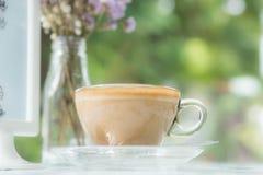 Καφές Cappuccino στο σαφές φλυτζάνι στον επιτραπέζιο καφέ στοκ εικόνες