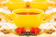 Καφές Espresso σε ένα κίτρινο φλυτζάνι, με φρούτα φραουλών, τα σταφύλια και την κανέλα στο μέτωπο, στο άσπρο υπόβαθρο Στοκ Εικόνες