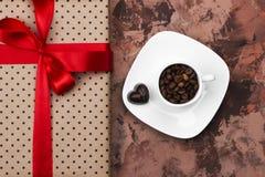 Καφές Espresso στο άσπρο φλυτζάνι, δώρο με το κώλυμα και σοκολάτες Στοκ Φωτογραφίες