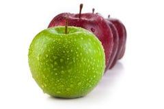 Καφέ μήλα που παρατάσσονται σε μια σειρά και μια πράσινη κινηματογράφηση σε πρώτο πλάνο μήλων Στοκ Φωτογραφίες