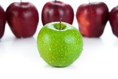 Καφέ μήλα που παρατάσσονται σε μια σειρά και μια πράσινη κινηματογράφηση σε πρώτο πλάνο μήλων Στοκ εικόνες με δικαίωμα ελεύθερης χρήσης