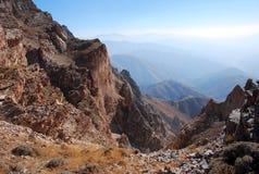 Καφετής βράχος στο υπόβαθρο του πανοράματος των βουνών της Τιέν Σαν στοκ εικόνες