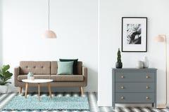 Καφετής καναπές με τα πράσινα μαξιλάρια που στέκονται στο άσπρο livi ανοιχτού χώρου στοκ φωτογραφία με δικαίωμα ελεύθερης χρήσης