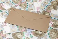 Καφετής κλειστός φάκελος στο υπόβαθρο 500 τραπεζογραμματίων PLN στοκ φωτογραφίες
