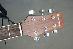 Καφετής λαιμός κιθάρων του Martinez με το συντονισμό των γόμφων σε ένα γκρίζο υπόβαθρο στοκ εικόνες