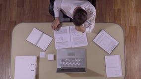 Καφετής-μαλλιαρός επιχειρηματίας που ελέγχει το κείμενο του εγγράφου του φιλμ μικρού μήκους