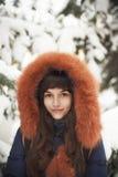 Καφετής-μαλλιαρό κορίτσι στην κουκούλα με τη γούνα που χαμογελά σε ένα υπόβαθρο των χιονισμένων δέντρων Στοκ φωτογραφία με δικαίωμα ελεύθερης χρήσης