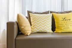 Καφετής σύγχρονος καναπές με τα κίτρινα μαξιλάρια στο καθιστικό Στοκ Εικόνες