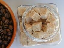 Καφετί καθαρισμένο βάζο κύβων ζάχαρης κοντά στα φασόλια καφέ στοκ εικόνες με δικαίωμα ελεύθερης χρήσης