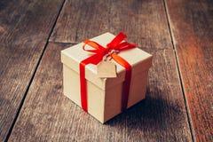 Καφετί κιβώτιο δώρων και κόκκινη κορδέλλα με την ετικέττα στο ξύλινο υπόβαθρο με το s Στοκ φωτογραφία με δικαίωμα ελεύθερης χρήσης