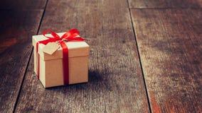 Καφετί κιβώτιο δώρων και κόκκινη κορδέλλα με την ετικέττα στο ξύλινο υπόβαθρο με το s Στοκ Εικόνα