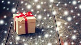 Καφετί κιβώτιο δώρων και κόκκινη κορδέλλα, χιόνι με την ετικέττα στο ξύλινο υπόβαθρο Στοκ Εικόνες