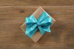 Καφετί κιβώτιο δώρων με το ανοικτό μπλε τόξο κορδελλών στον ξύλινο δρύινο πίνακα άνωθεν Στοκ Φωτογραφία