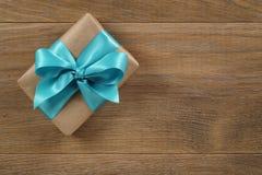 Καφετί κιβώτιο δώρων με το ανοικτό μπλε τόξο κορδελλών στον ξύλινο δρύινο πίνακα άνωθεν Στοκ φωτογραφίες με δικαίωμα ελεύθερης χρήσης